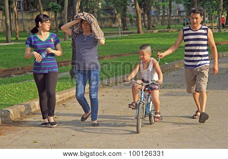 family of 4 peoples is walking in park, Hanoi, Vietnam
