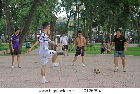 guys are playing a ball in park of Hanoi, Vietnam