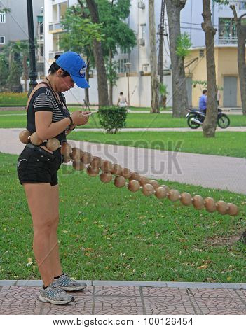 woman is exercising with hoop in park of Hanoi, Vietnam