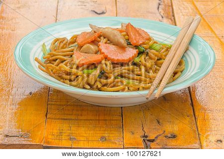 fried noodle with chopsticks  on wooden background