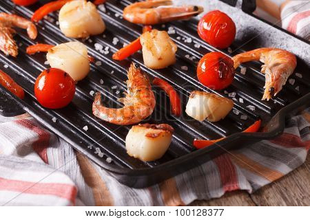 Scallops And Shrimp Are Fried On A Grill Pan Close-up. Horizontal