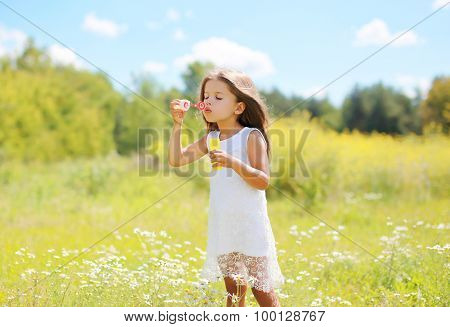 Child Blowing Soap Bubbles On Meadow In Sunny Summer Day
