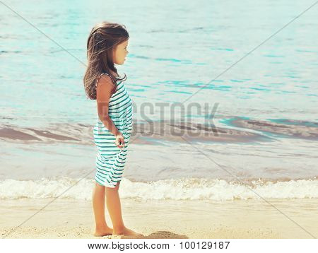 Little Girl Child Walks On The Beach Near Sea In Profile