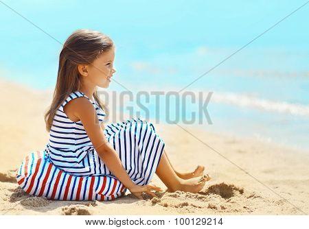 Little Girl Sitting On The Sand Beach Near Sea In Summer Day