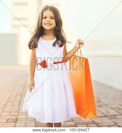 Portrait Of Beautiful Smiling Little Girl Wearing A Dress With Shopping Bag Outdoors