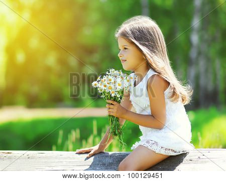 Portrait Of Cute Little Girl With Bouquet Of Chamomiles Flowers In Sunny Summer Day