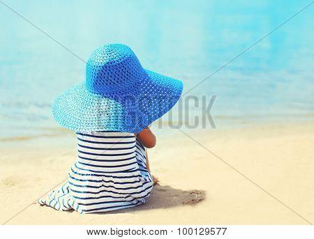 Pretty Little Girl In Striped Dress And Straw Hat Enjoying Summer On The Beach Near Sea