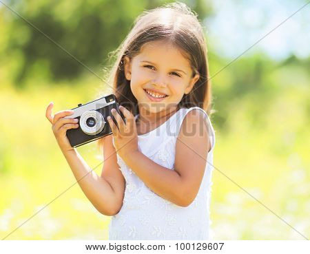 Sunny Portrait Of Cute Smiling Little Girl Child With Retro Vintage Camera In Summer Day