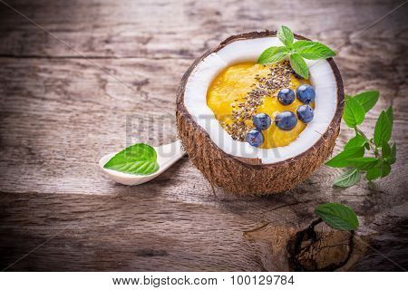 Mango smoothies for breakfast with a garnish of chia seeds in the shell coconut