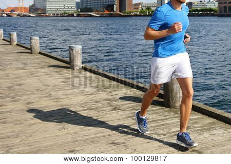 Low section of fit young man jogging on boardwalk. He is in sports clothing. Determined male jogger is exercising by river.