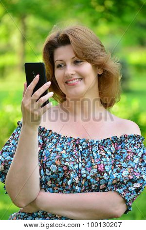 woman with a cell phone in nature at  the summer