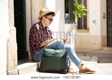 Traveling Man Sitting On Sidewalk Reading Map