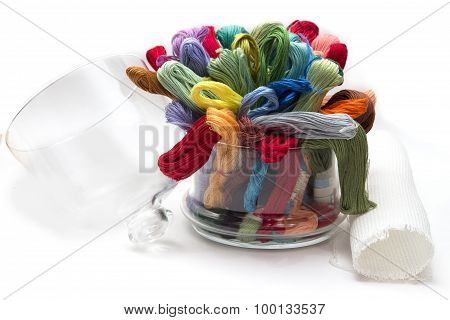 set of colored threads for embroidery, folded in a glass vase, on the white background fabric and la