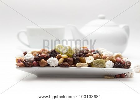 mixture of nuts and dried fruits are on the plate, background of the coffee maker, cups white closeu