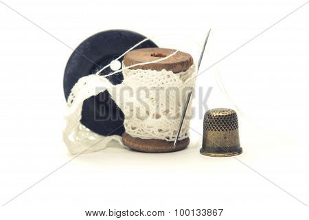 wooden vintage spool for thread wound with white lace for sewing, needle, black wooden button and a