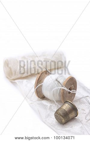 roll of white lace, a wooden spool of white cotton thread for sewing with needle and a metal thimble