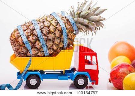 Pineapple With Tape-measure And Fruits On Lorry