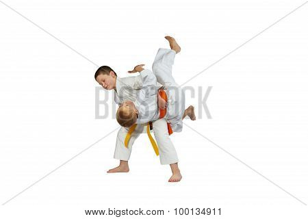 Young athletes train judo throws on a white background