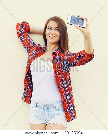 Fashion, Technology And People Concept - Happy Pretty Girl Wear A Checkered Red Shirt And Shorts Mak