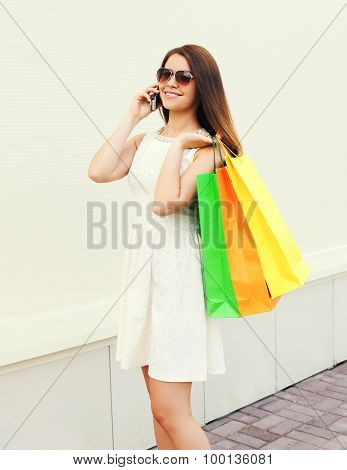 Happy Beautiful Young Smiling Woman With Shopping Colorful Bags Using And Talk On The Smartphone Out