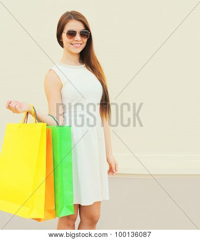 Portrait Of Beautiful Young Smiling Woman In White Dress And Sunglasses With Shopping Bags