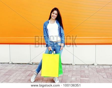 Beautiful Smiling Girl With Shopping Bags In Jeans Clothes Over Orange Wall