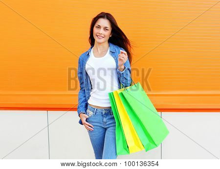 Beautiful Young Woman With Shopping Bags In Jeans Clothes Over Orange Wall
