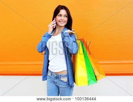 Portrait Of Happy Beautiful Young Smiling Woman With Shopping Colorful Bags In Jeans Clothes Talk On