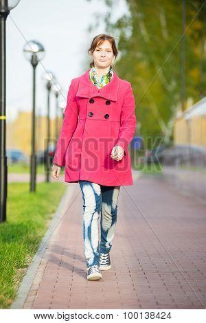 Beautiful woman in red coat walking autumn street.