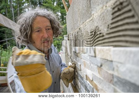 Workman About To Press An Ornamental Tile Into A Glue With His Fist