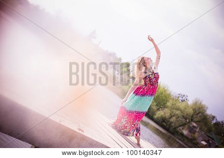 Vintage picture of gracious young woman dancing by lake