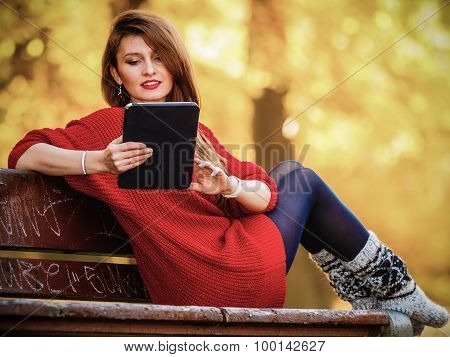 Woman In Autumn Park Using Tablet Computer Reading.