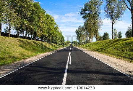 Black Serpentine Of Asphalt Road In Sunny Day.