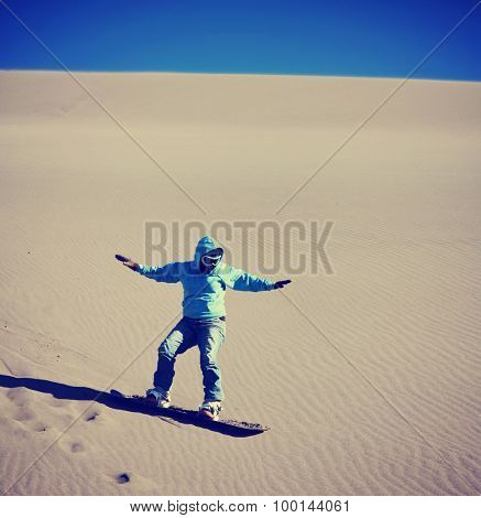 a woman sand boarding down a sandy dune hill with goggles and a sweatshirt hoodie on a snowboard toned with a retro vintage instagram filter effect app or action