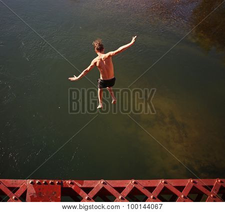 a boy jumping of an old train trestle bridge into a river toned with a retro vintage instagram filter effect app or action on a hot summer day