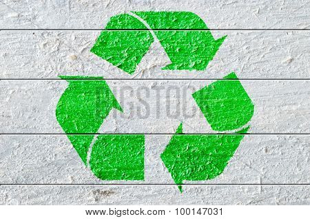 Green recycle symbol painted on a white natural textured wood.