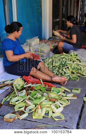 Bali, Indonesia, April 16, 2015. Undefined balinese women make offerings of palm leaves for the fest at the local temple in Bali, Indonesia