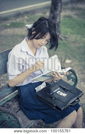Cute Asian Thai Schoolgirl Student In High School Uniform Is Sitting And Reading On The Bench With B