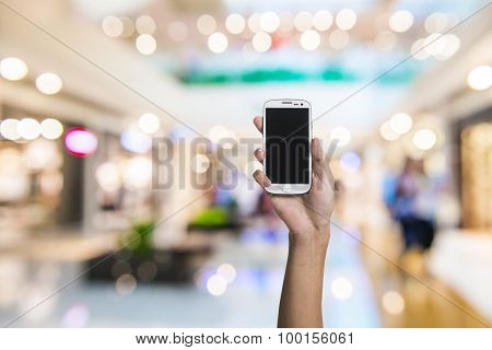 Using smartphone in a market or department store closeup image.