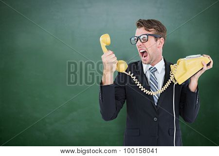 Geeky businessman shouting at telephone against green chalkboard