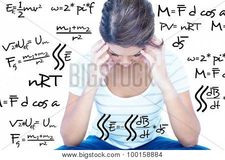 Pretty brunette with head on hands against maths equation