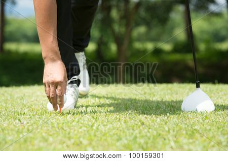 Golfer Placing Golf Ball On Tee On A Sunny Day At Course