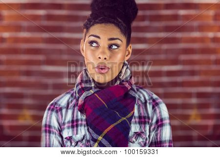 A beautiful happy hipster whistling against a red brick wall