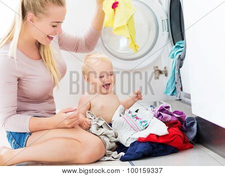 Mother and baby loading clothes into washing machine