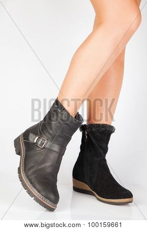 Beautiful female legs in black boots different on a white background