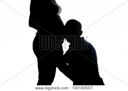 Silhouette of listening man and pregnant woman's belly