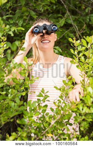 Smiling blonde looking through binoculars in the nature
