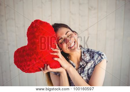 Pretty hipster holding heart pillow on wooden planks background