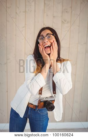 Pretty hipster using her vintage camera on wooden planks background
