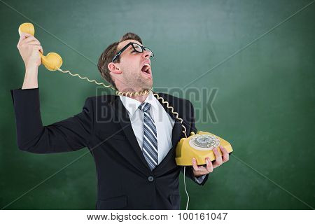 Geeky businessman being strangled by phone cord against green chalkboard